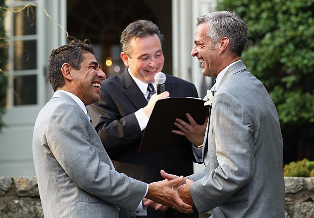 WASHINGTON - AUGUST 21:  TV reporter Roby Chavez (L) hold hands with his partner Chris Roe (R) during their wedding ceremony, officiated by Rev. Dwayne Johnson (C) of Metropolitan Community Church of Washington, August 21, 2010 at the Woodrow Wilson House in Washington, DC. Chavez of Matthews, Louisiana, and Roe, of Monticello, Wisconsin, tied the knot after they have been together for five years. Roe popped the question on the night when DC became the sixth place in the U.S. to legalize same-sex marriage while Chavez was on a tight deadline covering the story. The couple will spend two weeks in Greece for their honeymoon.  (Photo by Alex Wong/Getty Images)